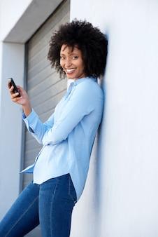 Belle jeune femme africaine avec un téléphone portable se penchant vers le mur en plein air
