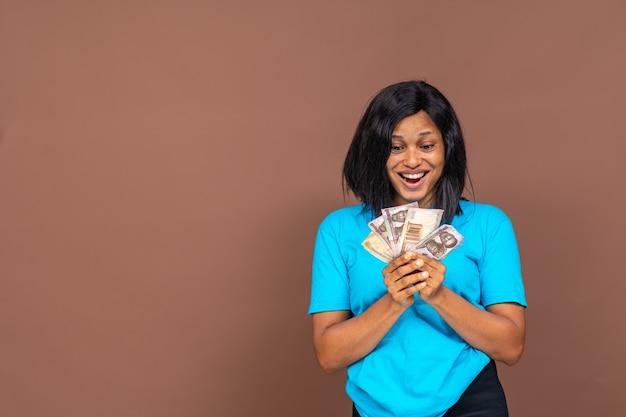 Belle jeune femme africaine tenant de l'argent dans sa main, avec un air de surprise sur son visage