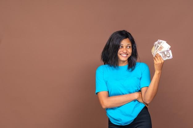 Belle jeune femme africaine tenant de l'argent dans sa main, avec un sourire sur son visage