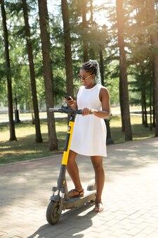 Belle jeune femme africaine à travers une application mobile prend un bail de pompe électrique
