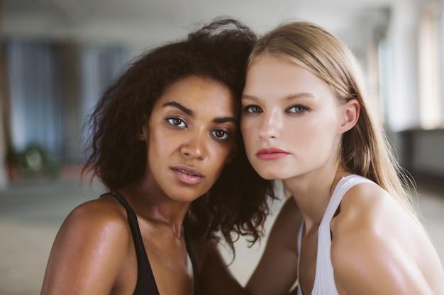 Belle jeune femme afro-américaine aux cheveux bouclés foncés et femme aux cheveux blonds pensivement tout en passant du temps ensemble
