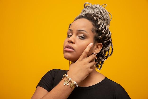 Belle jeune femme afro-américaine aux cheveux de la peur sur jaune