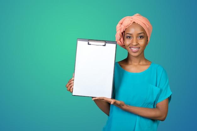 Belle jeune femme afro-américaine montrant le presse-papiers