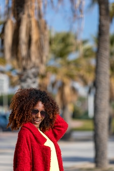 Belle jeune femme afro bouclée portant des lunettes de soleil et une veste rouge debout dans une rue de la ville tout en touchant les cheveux et souriant dans une journée ensoleillée