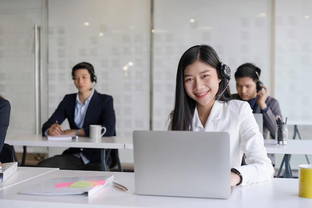 Belle jeune femme agent des services à la clientèle avec casque travaillant dans un bureau de centre d'appels. concept de soins de soutien à l'équipe du service client