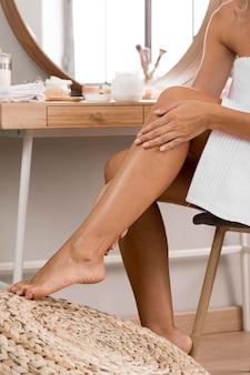 Belle jeune femme à l'aide de crème sur ses jambes