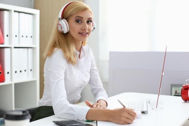 Belle jeune femme à l'aide d'écouteurs au travail