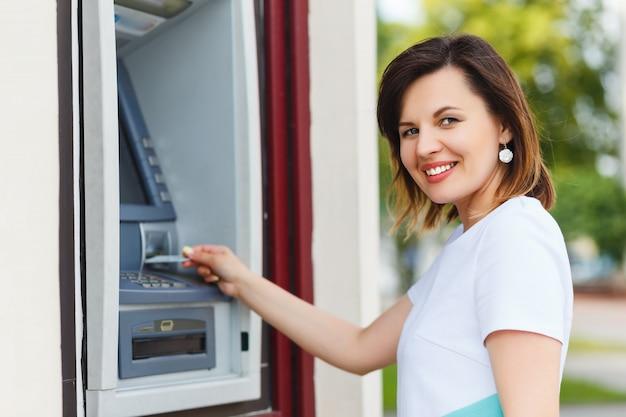 Belle jeune femme à l'aide d'un guichet automatique