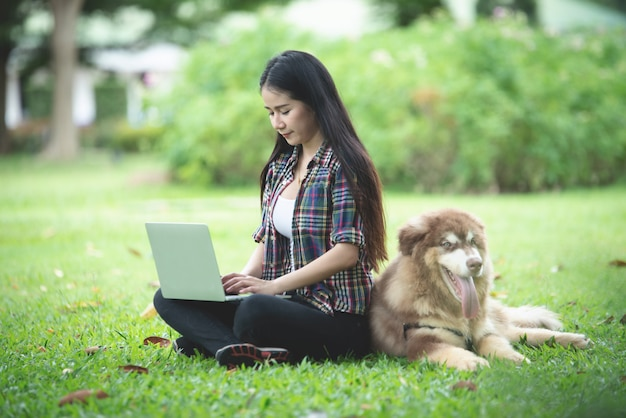 Belle jeune femme à l'aide d'un ordinateur portable avec son petit chien dans un parc en plein air. portrait de mode de vie.