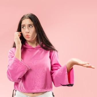 Belle jeune femme à l'aide de studio de téléphonie mobile sur studio de couleur rose.
