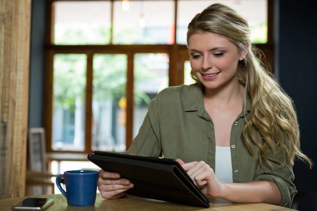 Belle jeune femme à l'aide de tablette numérique au café