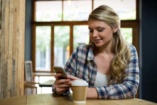 Belle jeune femme à l'aide de téléphone portable au café