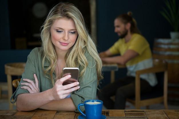 Belle jeune femme à l'aide de téléphone portable à table dans un café