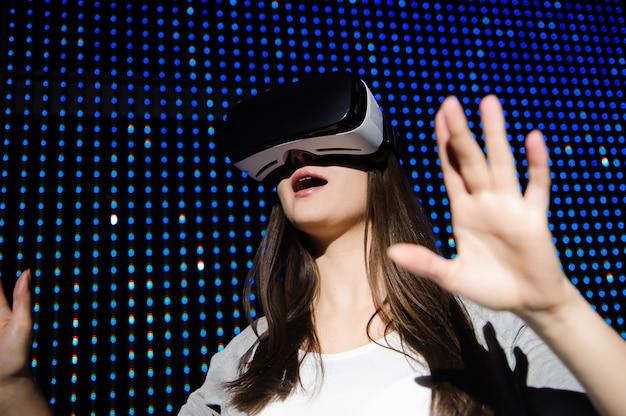 Belle jeune femme à l'aide de vr jouant des lunettes de casque vr pour le concept de réalité virtuelle