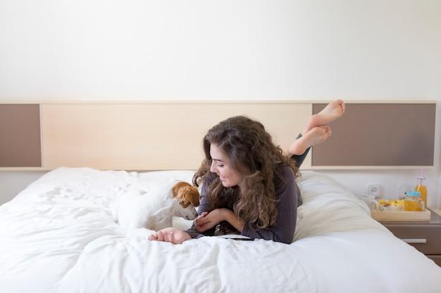 Belle jeune femme allongée sur le lit avec son mignon petit chien en plus. maison, intérieur et style de vie