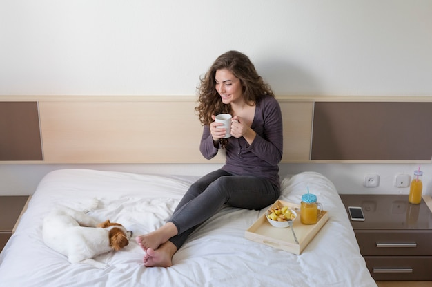 Belle jeune femme allongée sur le lit avec son mignon petit chien en plus.