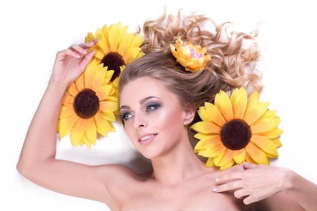 Belle jeune femme allongée parmi les fleurs d'un tournesol. soins de la peau et concept de mode de vie sain