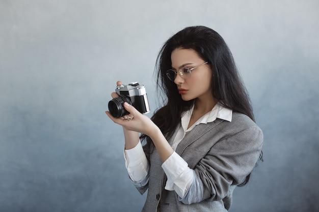 Belle jeune femme avec appareil photo à l'intérieur. portrait de jeune fille à la mode photographe