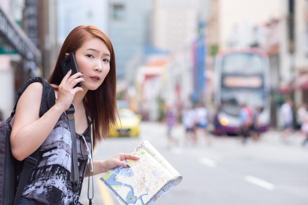 Belle jeune femme appelant un taxi public par téléphone en ville