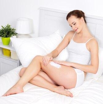 Belle jeune femme appliquant la crème pour la peau sur les jambes