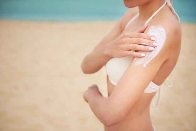 Belle jeune femme appliquant la crème solaire sur la plage