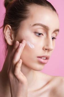 Belle jeune femme appliquant de la crème sur son visage rose
