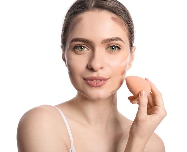 Belle jeune femme appliquant le maquillage contouring contre le blanc