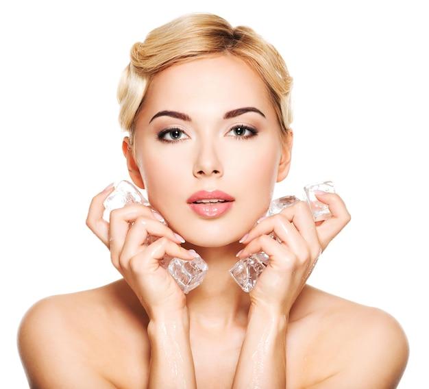 Belle jeune femme applique la glace au visage. concept de soins de la peau. isolé sur blanc.