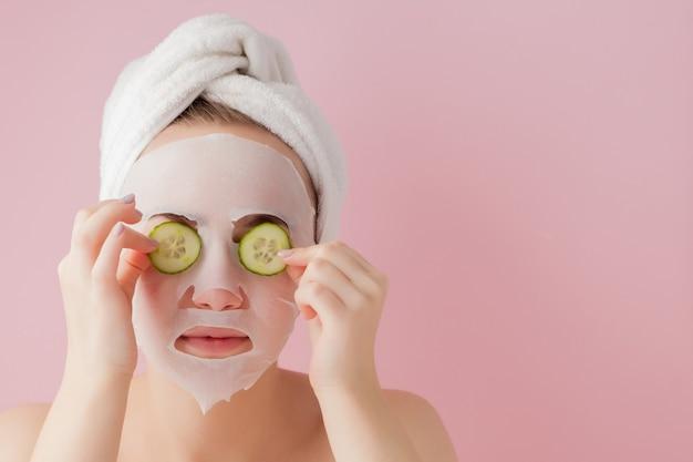 Belle jeune femme applique un masque de tissu cosmétique sur un visage avec du concombre sur un espace rose