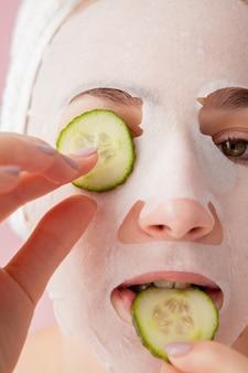 Belle jeune femme applique un masque de tissu cosmétique sur un visage avec du concombre sur rose