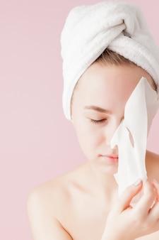 Belle jeune femme applique un masque de tissu cosmétique sur un visage sur un espace rose