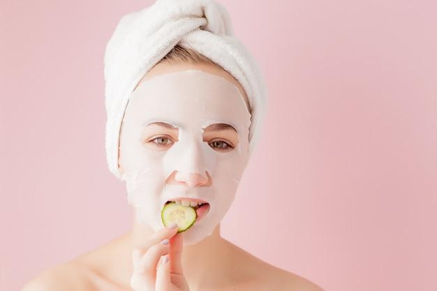 Belle jeune femme applique un masque de tissu cosmétique sur un visage rose