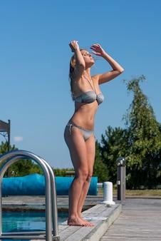 Belle jeune femme appréciant l'été près de la piscine