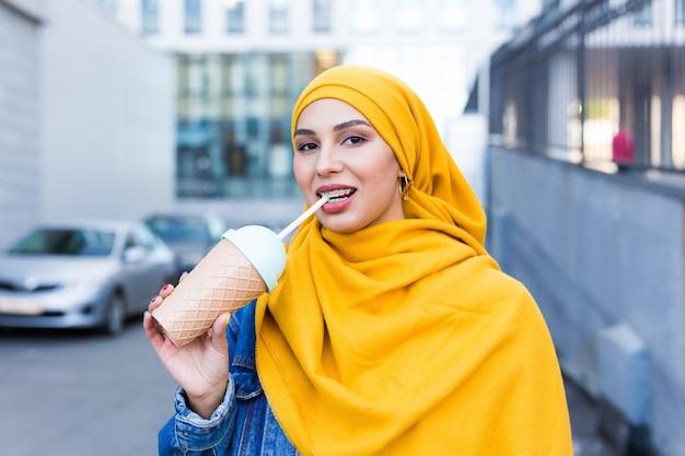 Belle jeune femme arabe en hijab, boire un cocktail de refroidissement en plein air.