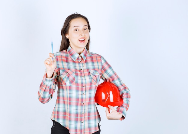 Belle jeune femme architecte tenant un casque de sécurité avec un stylo.
