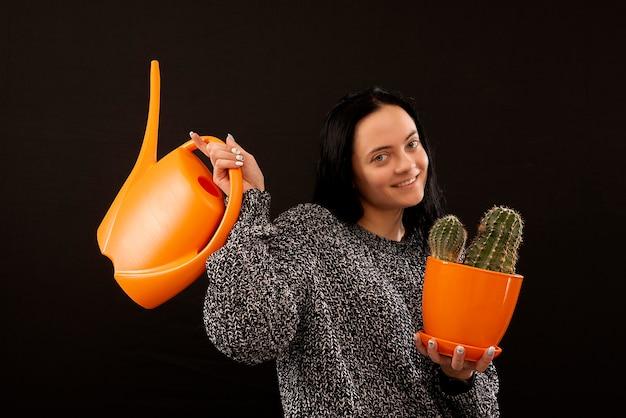 Belle jeune femme avec arrosoir et un cactus isolé sur une surface noire