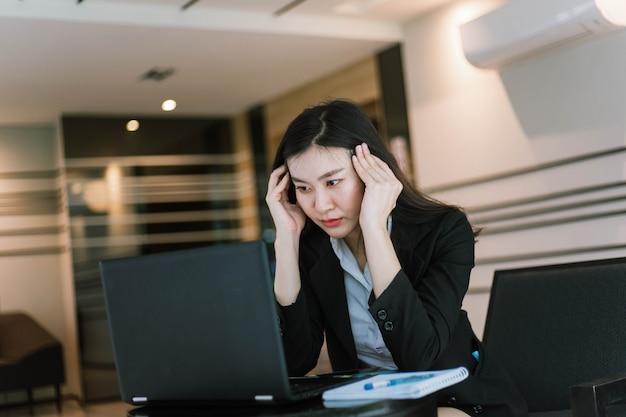 Belle jeune femme asiatique à l'aide de son ordinateur portable