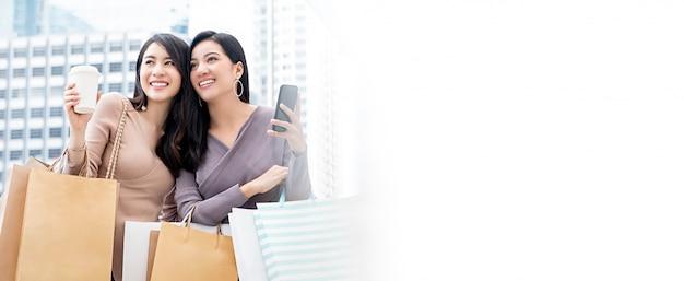 Belle jeune femme asiatique amis appréciant faire du shopping dans la ville