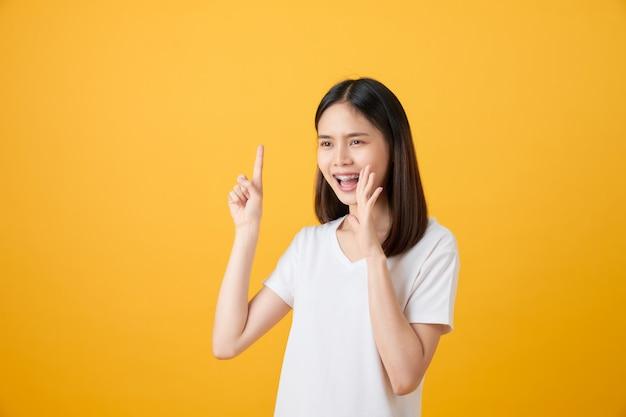 Belle jeune femme asiatique annonçant avec les mains à la bouche et racontant un secret, isolé sur fond orange clair