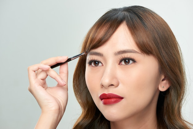 Belle jeune femme asiatique appliquant le pinceau de poudre cosmétique sur le sourcil, le maquillage naturel, le visage de beauté