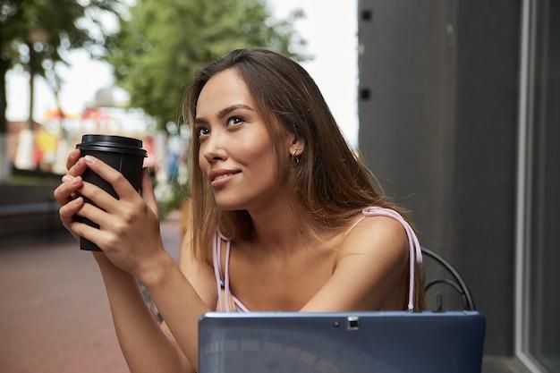 Belle jeune femme asiatique aux cheveux longs noirs, assise à table à l'extérieur avec un ordinateur portable, se reposant. étudiant prenant une tasse de café à l'extérieur du café après avoir fait ses devoirs. travail à distance, éducation en ligne