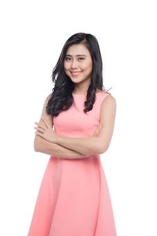 Belle jeune femme asiatique aux longs cheveux noirs en robe rose debout sur blanc.
