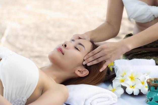 Belle jeune femme asiatique bénéficiant d'un massage à l'extérieur dans un salon spa
