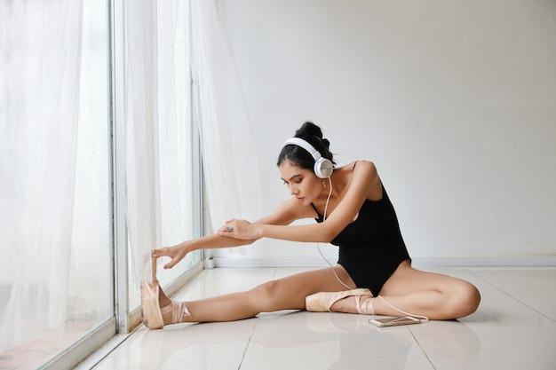 Belle jeune femme asiatique en bonne santé et sportive en tenue de sport noire assis avec un casque, écouter de la musique à partir de téléphone mobile tout en formant la danse classique sur le mur blanc .technologie et concept sain