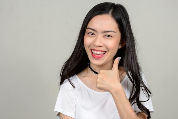 Belle jeune femme asiatique contre l'espace blanc