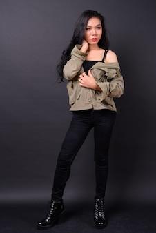 Belle jeune femme asiatique contre le mur noir