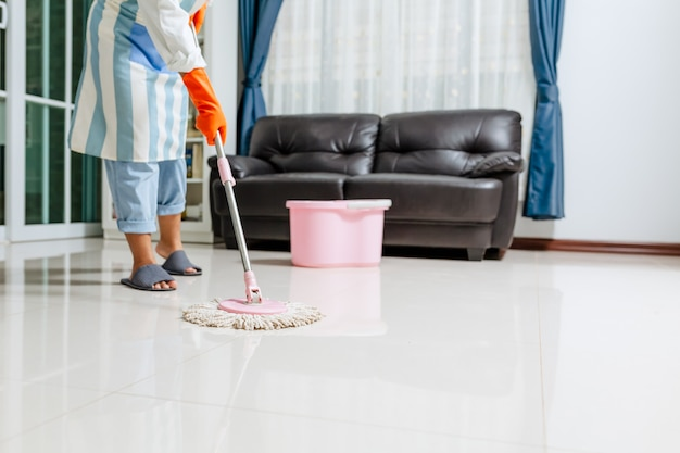 Belle jeune femme asiatique dans des gants de protection à l'aide d'un balai humide tout en nettoyant le sol dans la maison