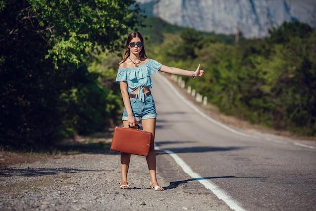 Belle jeune femme asiatique dans un style hippie. voyage en auto-stop. route dans les montagnes. l'idée et le concept des vacances d'été et de la liberté