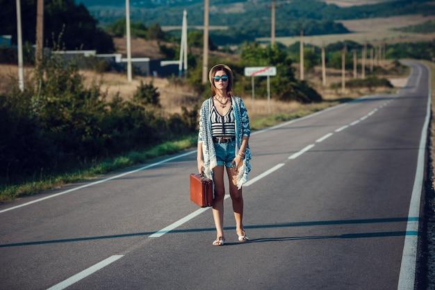 Belle jeune femme asiatique dans un style hippie. voyage en auto-stop. route dans les montagnes.