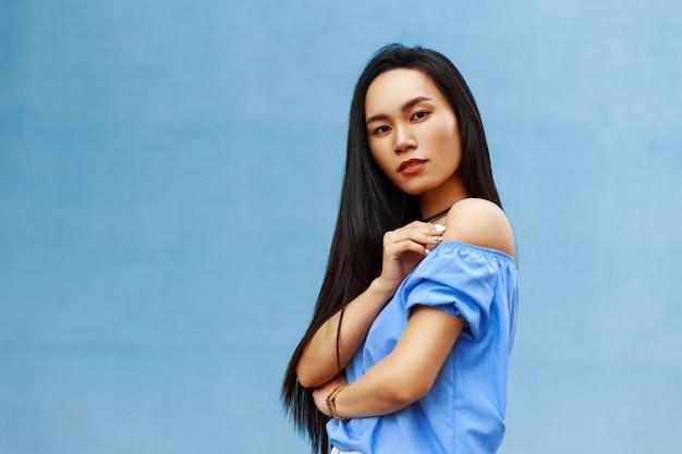 Belle jeune femme asiatique dans un vêtement d'été élégant pose près du mur bleu